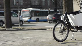 City life in Amsterdam. A bike at the foreground and traffic in the distance. The Netherlands stock video footage