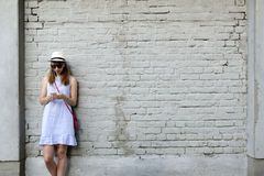 City life concept. Young woman standing next to the white brick wall listening to music in headphones.  Royalty Free Stock Image