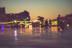 City life evening lights blur, sunset and pedestrian. Defocused city life view with sunset, bokeh and silhouettes. Captured in Tirana center at Skanderbeg Square Royalty Free Stock Photo