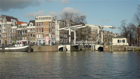 City life. Historic canal houses, bridge and traffic in Amsterdam. City life. Historic canal houses, an old bridge and traffic in Amsterdam. People are passing stock footage
