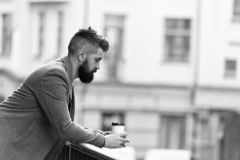 City lifestyle. Businessman well groomed appearance enjoy coffee break out of business center urban background. Relax. And recharge. Man bearded hipster drink stock image