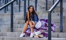 Young woman with bunch of books sitting on stairs in urban in blue jeans jacket royalty free stock photos