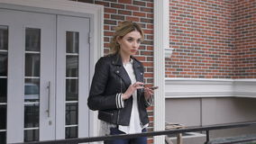 City lifestyle stylish girl using a phone texting on smartphone app in a street. blonde. In a black leather jacket stock video footage