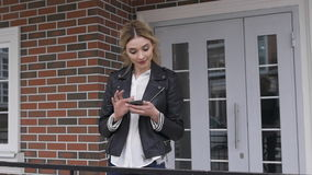 City lifestyle stylish girl using a phone texting on smartphone app in a street. blonde. In a black leather jacket stock footage