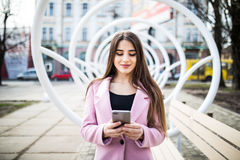City lifestyle stylish girl using a phone texting on smartphone app in a street Royalty Free Stock Photography
