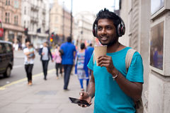 City lifestyle. Young man in the street with a coffee, headphones and mobilephone Stock Photos