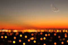 City lights. Soft focus city lights with moon showing at sunset Stock Photo