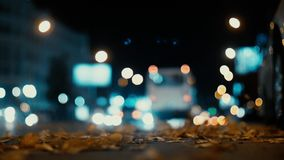 City lights and cars driving in traffic background. Autumn leaves scatter along the night road from the wind from passing cars. Out of focus background with stock video