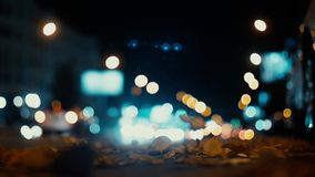 City lights and cars driving in traffic background. Autumn leaves scatter along the night road from the wind from passing cars. Out of focus background with stock footage
