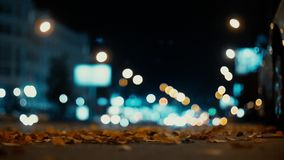 City lights and cars driving in traffic background. Autumn leaves scatter along the night road from the wind from passing cars. stock video footage