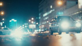 City lights and cars driving in traffic background. Autumn leaves scatter along the night road from the wind from passing cars. Out of focus background with stock video footage