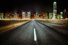 City lights. Empty road at night with a city lights in the background Royalty Free Stock Photos