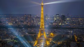 City lights of Paris, illuminated Eiffel Tower and skyscrapers, dusk to night