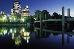 City lights reflect in river. Bright city lights of Calgary, Alberta, Canada in early evening with dramatic reflection on the river royalty free stock images