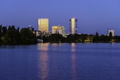 City lights reflecting at night over the water of Herastrau lake stock photography