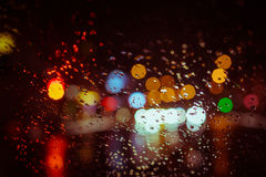City lights seen through the car windshield. In rainy weather with focus on some water drops. Night time. Abstract background Stock Image