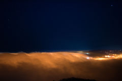 City lights under thick layer of fog. City of Kavala, Greece covered by a thick layer of cloud Stock Photo