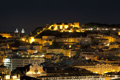 City of Lisbon with Castle of Sao Jorge illuminated at night Royalty Free Stock Images