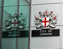 City of London Crest. LONDON - JUNE 18: The City of London Crest and sign on the side of a building with the reflection in the adjoining window on June 18, 2010 Stock Images