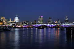 City Of London skyline at dusk. City of London, UK skyline at dusk, illuminated, with reflections in river Stock Photography
