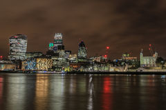 City of London skyline at night. With reflections in the water Stock Image