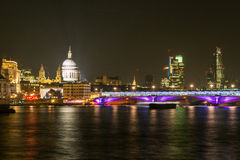 London skyline at night. Scenic view of the London skyline at night with the river Thames in the foreground, England Stock Photos