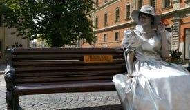 The city Lviv in Ukraine. LVIV, UKRAINE - AUGUST 25: Entertainment for the tourist in Lviv - living statue, silver girl on August 25, 2011 in Lviv, Ukraine Royalty Free Stock Photography