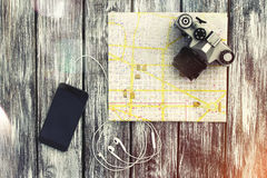 City map with a smartphone, headphones and vintage camera. City map on the background of vintage boards, with a smartphone, headphones and vintage camera. Lens Stock Images