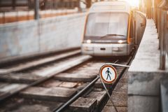 City metro train comes from underground tunnel to street. Tilt-shift view of modern glossy subway train or city tram coming from underground tunnel into outdoor Royalty Free Stock Photo