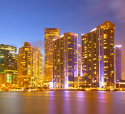 City of Miami Florida, night skyline. Cityscape of residential and business buildings illuminated at sunset with reflection Stock Images