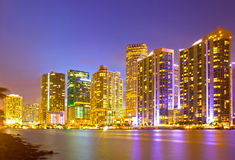 City of Miami Florida, night skyline. Cityscape of residential and business buildings illuminated at sunset with reflection Royalty Free Stock Images