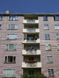 City: modernist apartment block. Detail of balconies with flowers in modernist apartment block Royalty Free Stock Photos