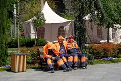 City municipal workers are sitting on a bench for short break   after cleaning the city street in april sunny day stock photo