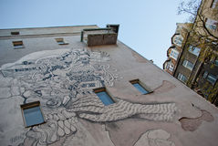 City mural. On a grey wall and a part of a well-maintained tenement house in the background presenting contrasts. City of Lodz, Poland Royalty Free Stock Photos