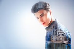 Nice young man thinking about the river. In the city. Nice thoughtful young man standing and thinking about the river in the city while looking at you Royalty Free Stock Images