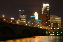 City at night. Minneapolis downtown skyline at night with Third Avenue Bridge in foreground stock photo