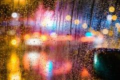 City Night bokeh. Car windshield. Rain Drops on window with light bokeh effect Stock Images
