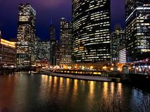 City night lights reflect onto a nearly frozen Chicago River in the loop during winter evening rush hour. stock photos