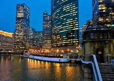 City night lights reflect over freezing Chicago River and el train passing over Lake Street in winter. Snow covered sidewalks. Stairs leading to river Stock Photos