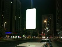 City at night with Rectangular outdoors advertising space - White screen Mockup royalty free stock image