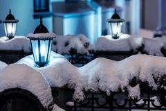 City night scene with street christmas lights during snowfall stock image