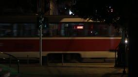 City at night, tramway, people walking, general shot. City at night, red tramway passing from right to left, crowd of people walking, general shot stock footage