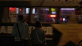 City at night, tramway, people walking. City at night, red tramway passing from right to left, crowd of people walking, medium shot stock footage
