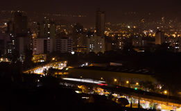 City night view. Night view of Sao Leopoldo City - Brasil, in the foreground the train is passing and it is possible to see only its lights due to long exposure Royalty Free Stock Photo