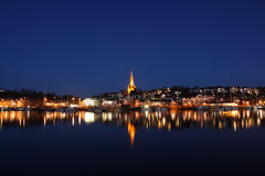 City at night with waterfront. The city Flensburg in Germany at night. The lights of the town are reflected by the water. The sky is clear and blue and some star royalty free stock photography