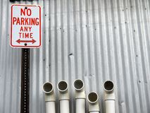 City: No Parking sign with pipes. No Parking sign with plastic pipes against corrugated iron wall Stock Image