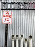 City: No Parking sign with pipes v. No Parking sign with plastic pipes and vintage lettering against corrugated iron wall Stock Photography