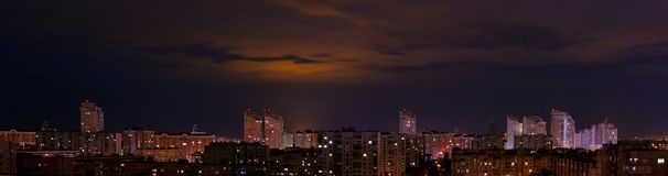 City panorama from above. The night sky with the moon through the clouds above the panorama of the sleeping area of the city of eastern Europe Stock Image