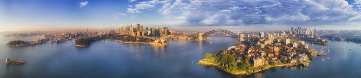 City Panorama. Wide elevated panorama of Sydney city landmarks around blue waters of Harbour on a sunny morning with blue sky reflecting in still waters Stock Photo