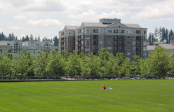 City Park. Apartment buildings border a city park where two women relax in the sun Stock Images